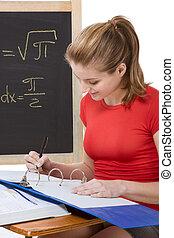 Caucasian schoolgirl by desk studying math exam