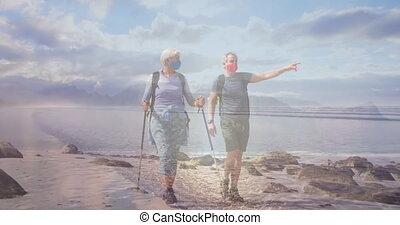Caucasian senior couple in face masks hiking on the coast, over moving sea
