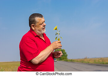 Caucasian senior in red shirt taking wild sunflower while standing on a roadside