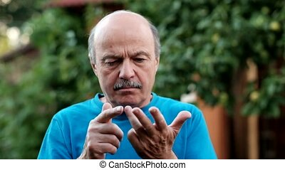 Caucasian senior man counting on fingers till five standing...