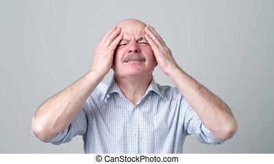 Caucasian senior man having terrible headache. Problem with...