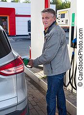 Caucasian senior man refueling vehicle on gas station at summer season