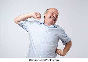 Caucasian senior man wearing blue shirt stretching his body awaking after sleep.