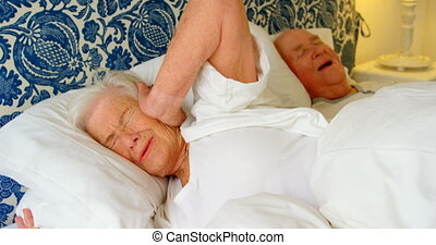 Caucasian senior woman getting disturbed with man snoring on bed at comfortable home. She is covering her ears 4k