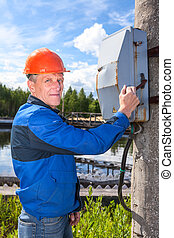 Caucasian senior worker man turning the power switch in an industrial plant