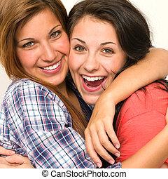 Caucasian sisters embracing,  laughing at camera