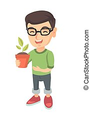 Caucasian smiling boy holding a potted plant.