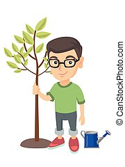 Caucasian smiling boy in glasses planting a tree.