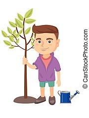 Caucasian smiling boy planting a tree.
