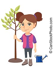 Caucasian smiling girl planting a tree.