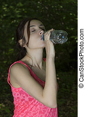 Caucasian sporty woman drinking water before sports