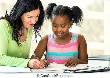 Caucasian teacher helping little african student at desk with school work.