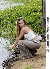 Caucasian Teen Girl Squatting On River Bank