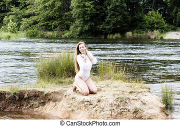 Caucasian Teen Woman Kneeling Along River In White Leotards