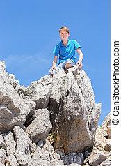Caucasian teenage boy sitting on top of rocks
