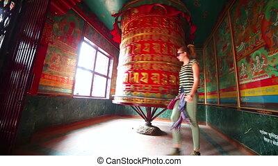 Caucasian tourist girl spinning at Prayer wheel - Female...
