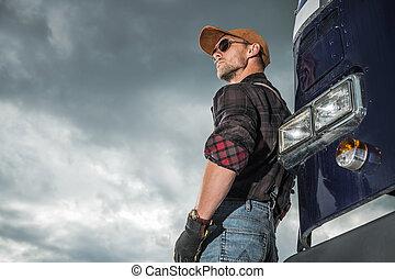 Caucasian Trucker Driver in Front of His Retro Semi Truck