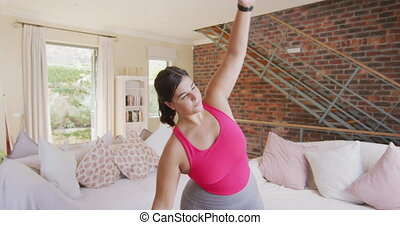 Caucasian female vlogger spending time at home, stretching up during exercises. Social distancing and self isolation in quarantine lockdown.