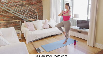 Caucasian female vlogger spending time at home, exercising yoga on a mat, using a laptop computer. Social distancing and self isolation in quarantine lockdown.