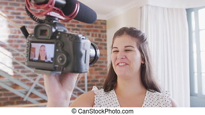Caucasian female vlogger spending time at home, holding a camera, preparing video for her vlog. Social distancing and self isolation in quarantine lockdown.