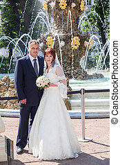 Caucasian wedding couple standing against beauty fountain