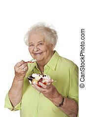 A beautiful elderly Caucasian woman eating a banana split icecream