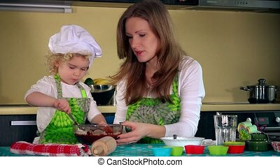 Caucasian woman and cute daughter cooking in kitchen. Family...