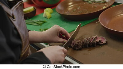 Caucasian woman cutting meat - High angle side view mid...