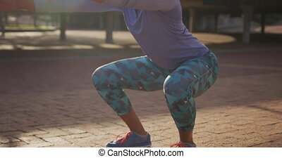 Caucasian woman doing squats in a park - Side view close up ...