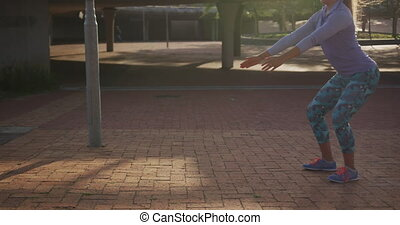 Caucasian woman doing squats in a park - Side view of a ...