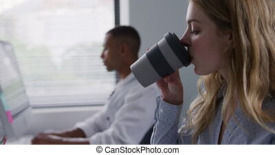 Caucasian woman drinking while working