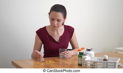 Caucasian woman drinks a lot of pills. Preventive medicine. Food supplements