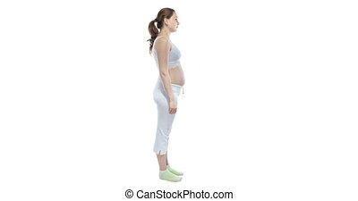 Caucasian woman during pregnancy with bare belly on white background, monthly shooting
