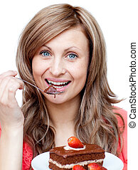 Caucasian woman eating a cake against a white background