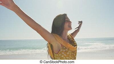 Caucasian woman enjoying the fresh air at beach - Side view ...