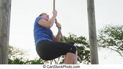 Caucasian woman exercising at bootcamp - Low angle side view...