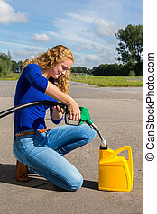 Caucasian woman fueling jerrycan with petrol