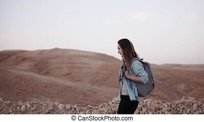 Caucasian woman hiking in desert. Slow motion. Tourist girl...