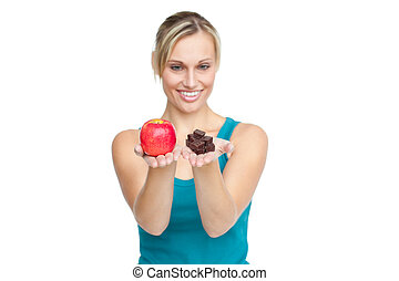 Caucasian woman holding an apple and chocolates
