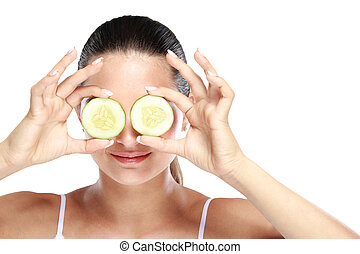 caucasian woman holding slices of cucumber for make up mask