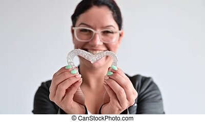 Caucasian woman holding two transparent heart-shaped aligners.