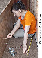 Caucasian woman housewife assembly furniture at home using Allen key.