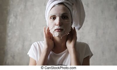 Caucasian woman in a moisturizing mask on her face knots a white towel on her head and looks at the camera. Cleansing Facial, Rejuvenation, Makeup and Relax 4k slow mo