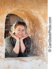 Caucasian woman in ancient wall window cheerful and happy