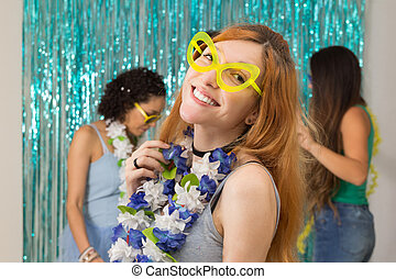 Caucasian woman is wearing funny glasses. In the background a carnival party