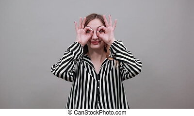 Caucasian woman looking at camera, doing glasses gesture with fingers on eyes