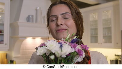 Caucasian woman looking at camera with flowers