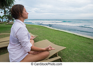caucasian woman meditates sitting in chair on the beach