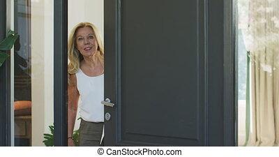 Caucasian woman opening the entrance door - Senior Caucasian...