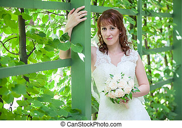 Caucasian woman portrait with green fence
